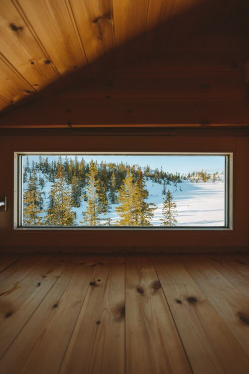 vertical-shot-of-a-cozy-attic-with-a-window-with-the-view-of-a-forest-covered-with-snow-in-norway